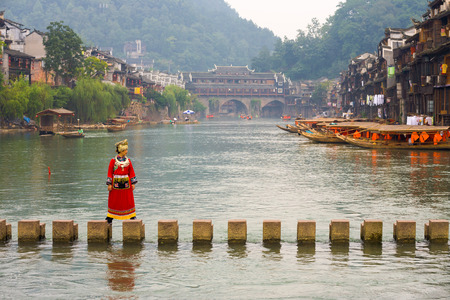 Fenghuang, China - September 12, 2007: A Chinese female tourist in traditional minority clothes crossing the stepping stone bridge across the Tuojiang River