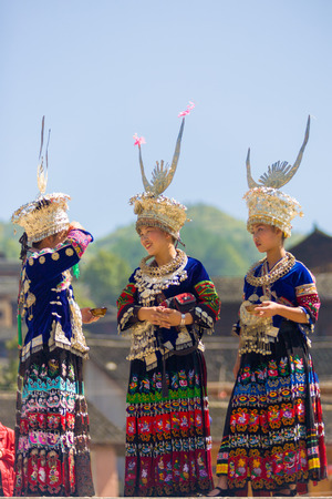 Xijiang, China - September 15, 2007: Three ethnic minority Miao women in traditional clothes and silver headdress wait for festival to start at Miao village in Xijiang, Guizhou, China Editorial