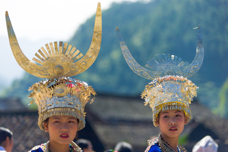 Xijiang, China - September 15, 2007: Miao women wearing traditional silver horn headdress and festival regalia wait for ceremony to begin at Xijiang ethnic minority Miao village in Guizhou, China