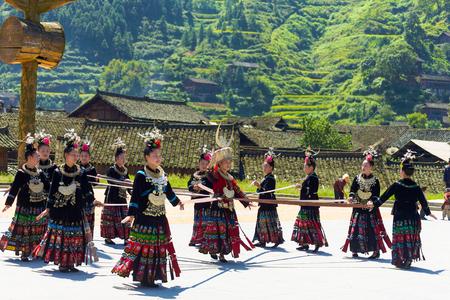 Xijiang, China - September 15, 2007: Miao women use a ribbon and dance wearing full traditional festival regalia and colorful costume at Xijiang ethnic minority Miao village, Guizhou, China
