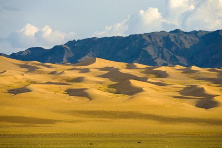 Geleidelijk aflopend, pittoreske zandduinen van de Mongoolse Gobi-woestijn en bergketen bij Khongor Els in Zuid-Mongolië