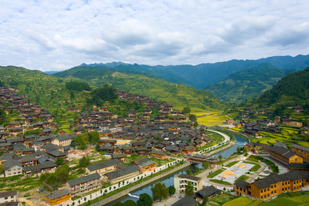 High angle view of the river and mountains behind the traditional wooden houses of Xijiang Miao ethnic minority village in Guizhou, China