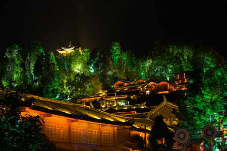 Old town buildings and hilltop pagoda lighted at night in the picturesque Chinese village of Lijjiang, Yunnan, China. Horizontal