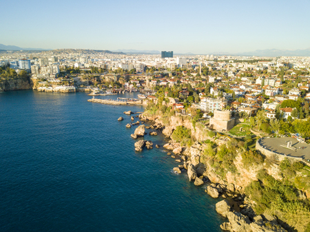 Aerial drone view along coastline below Hidirlik Castle toward Kaleici old town harbor in Antalya, Turkey
