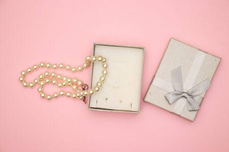 Present box with jewelry  on pink background 免版税图像