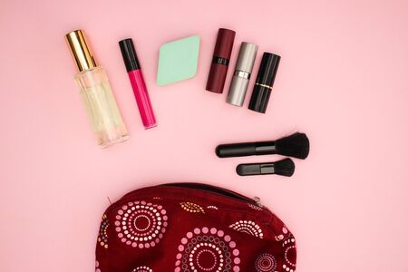 Vanity case with beauty products and cosmetics for woman on pink background