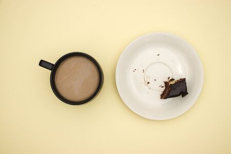 Cup of coffee and chocolate cake on yellow background 版權商用圖片