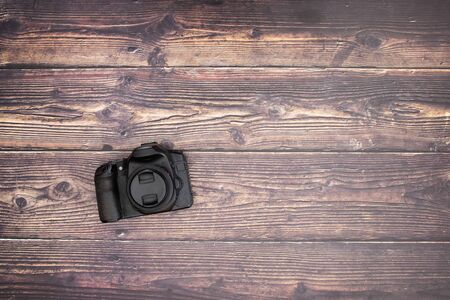 Black camera on the wooden background