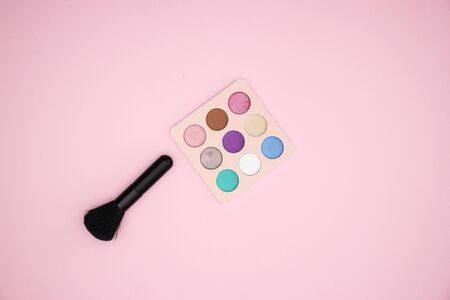 Eye shadow and make up brush on pink background