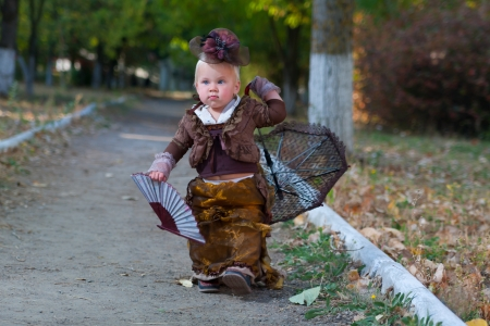 little lady in the autumn park and ancient clothes walks photo