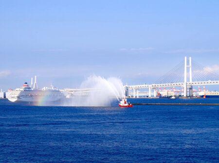 A fireboat giving the MS Asuka II Yokohama a water salute as she steams out of the Port of Yokohama. 版權商用圖片