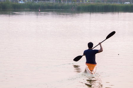 a man rowing in the canoe photo