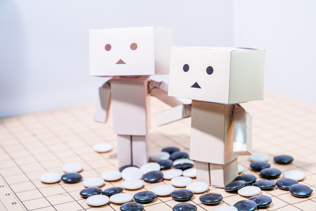 Box doll and Go game board Stock Photo