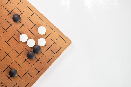 Game's white and black stone on cross board.