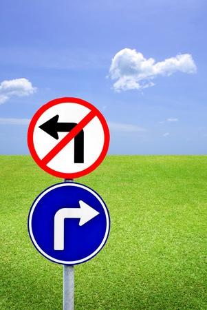 Turn left and do not turn right sign with blue sky and meadow photo
