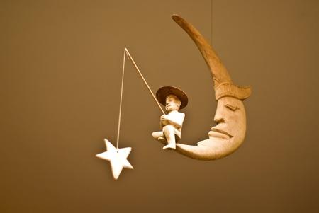 hombre pescando: Hombre de pesca de la estrella en la Luna, el juguete m�vil Foto de archivo