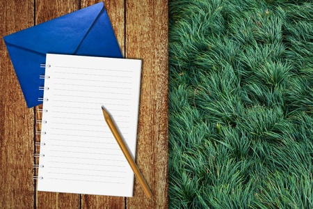 Notebook on wooden floor with green grass background photo