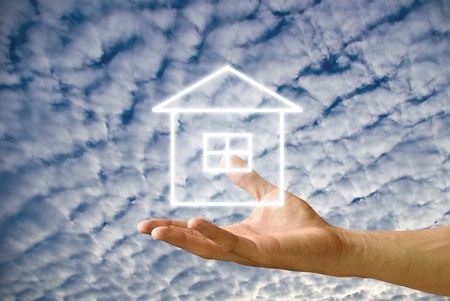 House icon in the hand with cloudy sky background photo