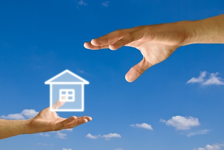 Small hand give the house icon to big hand with blue sky background photo