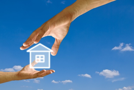 Big hand give the house icon to small hand with blue sky background photo