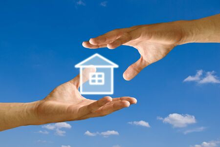 Hand take the house icon from other hand with blue sky photo