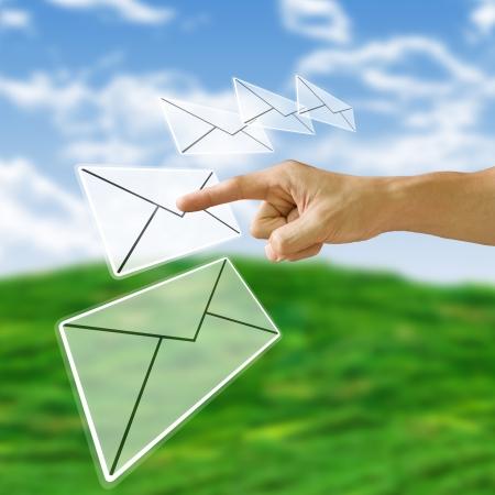 newletter: Dito spingendo la lettera con sfondo di natura, concetto di Email Archivio Fotografico