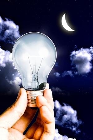 incandescence: Blue lamp bulb in the hand shine the light with moon and sky background