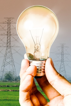electricity pole: Light bulb in the hand with electricity post background, Save energy and power concept Stock Photo