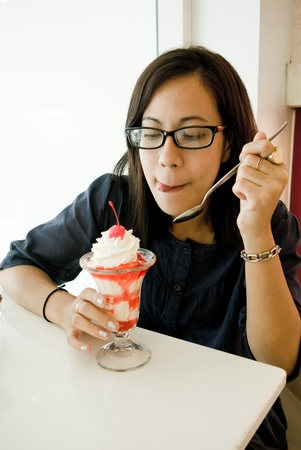 asian flavors: Asian women eating ice cream on the table Stock Photo