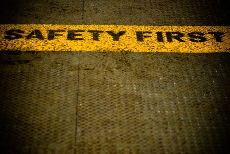 Safety first sign words on the metal ground