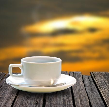 Kopje koffie op de houten tafel met zonsondergang hemelachtergrond