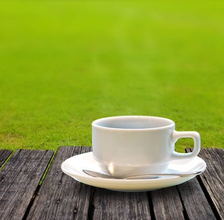 Hot coffee on wooden table with green grass background
