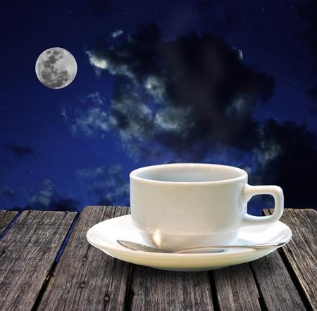 Hete koffie op houten tafel in de nacht, met volle maan achtergrond Stockfoto