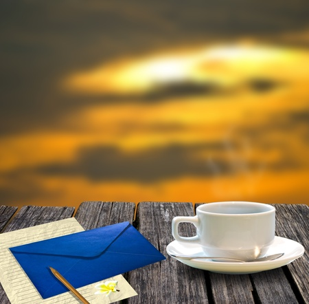 Coffee cup and letter on the wooden table with sunset sky background photo