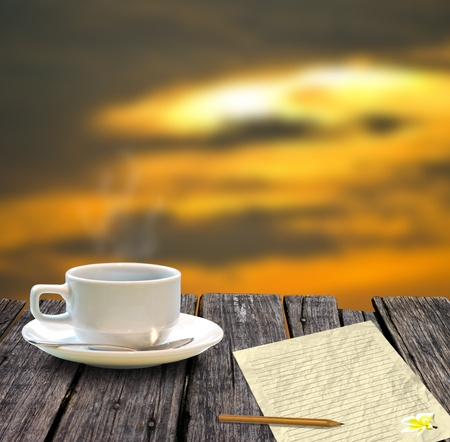 Coffee cup and letter on the wooden table with sunset sky background