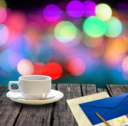 Hete koffie en brief op houten tafel met kleurrijke bokeh achtergrond, Letter concept.