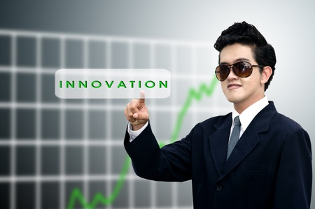 Yong businessman pushed the innovation button with graph background photo