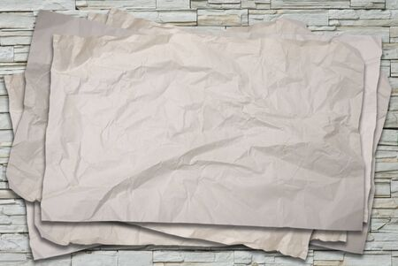 Old crumpled paper on stone wall background  photo