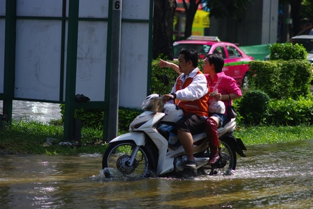 BANGKOK, THAILAND - NOV 7 : UNIDENTIFIED MAN AND WOMEN RIDE THE MOTORBIKE ON THE ROAD WITH WATER FLOOD ON NOV 7, 2011 IN KAMPHAENG PHET INTERSECTION, BANGKOK, THAILAND. THE BIG FLOOD IN BANGKOK