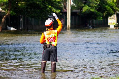 thailand flood: BANGKOK, THAILAND - NOV 7 : UNIDENTIFIED POLICEMAN WORKING IN WATER FLOOD ON NOV 7, 2011 IN KAMPHAENG PHET INTERSECTION, BANGKOK, THAILAND. THE BIG FLOOD IN BANGKOK