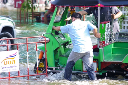 shove: BANGKOK, THAILAND - NOV 7 : UNIDENTIFIED DRIVER SHOVE TUK TUK IN WATER FLOOD ON NOV 7, 2011 IN KAMPHAENG PHET INTERSECTION, BANGKOK, THAILAND. THE BIG FLOOD IN BANGKOK
