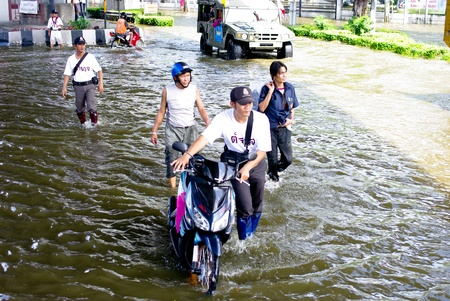 inconvenient: BANGKOK, THAILAND - NOV 7 : UNIDENTIFIED POLICEMAN HELP PEOPLE CARRY MOTORBIKE IN WATER FLOOD ON NOV 7, 2011 IN KAMPHAENG PHET INTERSECTION, BANGKOK, THAILAND. THE BIG FLOOD IN BANGKOK