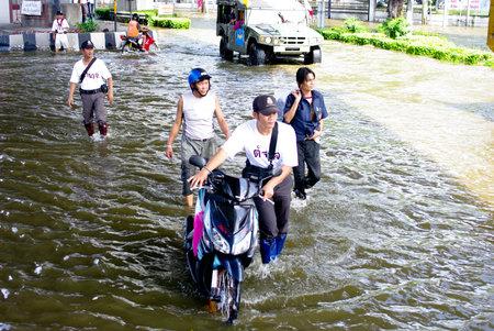 thailand flood: BANGKOK, THAILAND - NOV 7 : UNIDENTIFIED POLICEMAN HELP PEOPLE CARRY MOTORBIKE IN WATER FLOOD ON NOV 7, 2011 IN KAMPHAENG PHET INTERSECTION, BANGKOK, THAILAND. THE BIG FLOOD IN BANGKOK