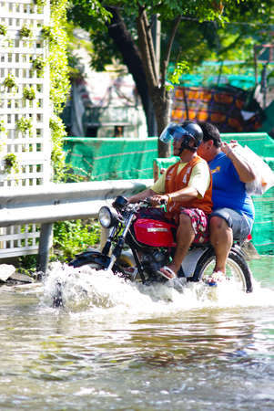 worst: BANGKOK, THAILAND - NOV 7 : Unidentified man to ride motorbike  through flooded road on Nov 7, 2011 at Kamphaeng Phet Intersection in Bangkok. This is the worst flood in the history of Thailand