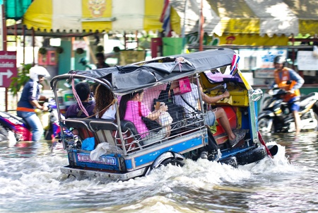 inconvenient: BANGKOK, THAILAND - NOV 7 : Unidentified Tuk tuk driver to ride his motor tribicycle through flooded road on Nov 7, 2011 at Kamphaeng Phet Intersection in Bangkok. This is the worst flood in the history of Thailand