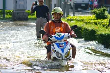 BANGKOK, THAILAND - NOV 7 : Unidentified man to ride motorbike  through flooded road on Nov 7, 2011 at Kamphaeng Phet Intersection in Bangkok. This is the worst flood in the history of Thailand