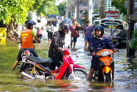 BANGKOK, THAILAND - NOV 7 : Unidentified man pushes his motorbike  through flooded road on Nov 7, 2011 at Kamphaeng Phet Intersection in Bangkok. This is the worst flood in the history of Thailand