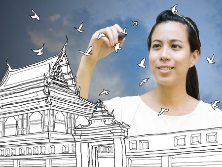 Cute girl drawing Ancient Thai architecture on board with blue sky background photo
