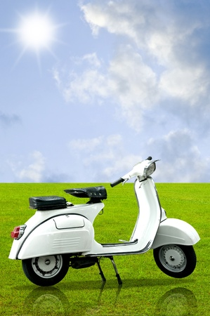 White retro vespa on grass in the garden with sky photo