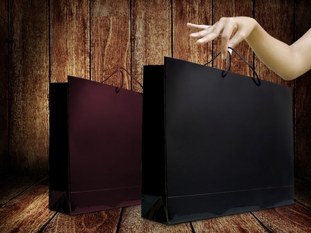 Glaze shopping bag in lady hand with wooden display background photo